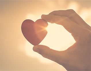 Hand holding up heart with rays of sunshine shinning through