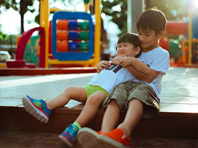 Two young brothers hugging at a playground
